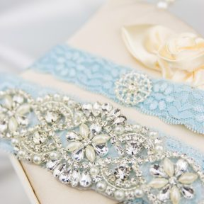 blue lace bridal garter two piece set with an arrangement of pearls and rhinestones