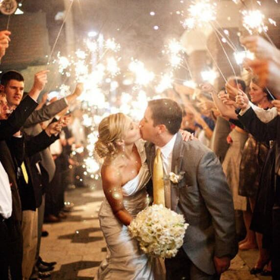 bride and groom kissing with giant wedding sparklers 70cm lit around them