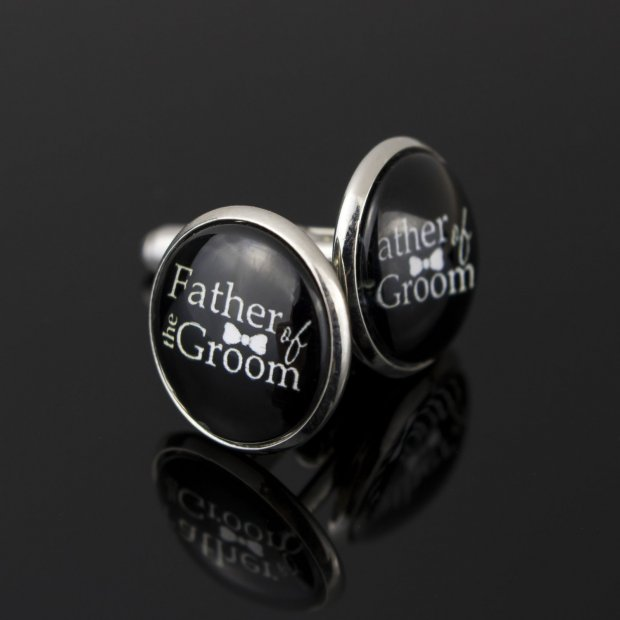 black round cufflinks with father of the groom written in white including a small bow tie in between the words
