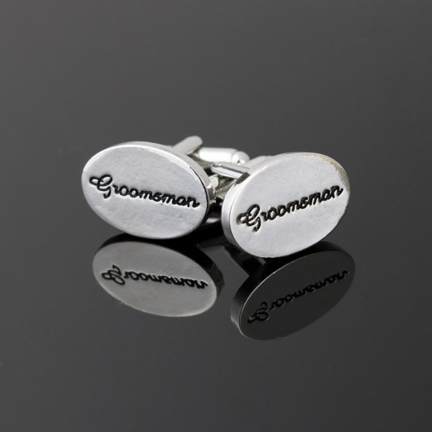 silver oval shaped cufflinks with groomsman written in black cursive and debossed in the metal